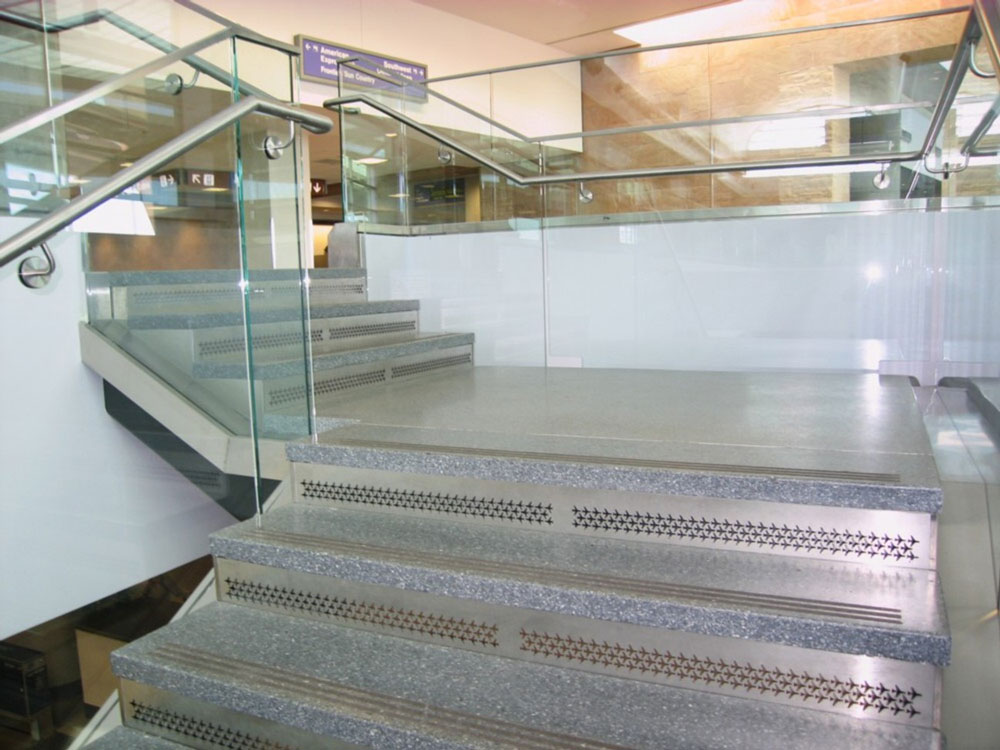 Tucson Airport. Stainless steel custom perf panel risers and glass guardrail.