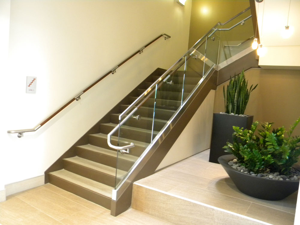 Rivulon - glass in shoe with stainless steel cladding. Stainless steel and wood handrail.