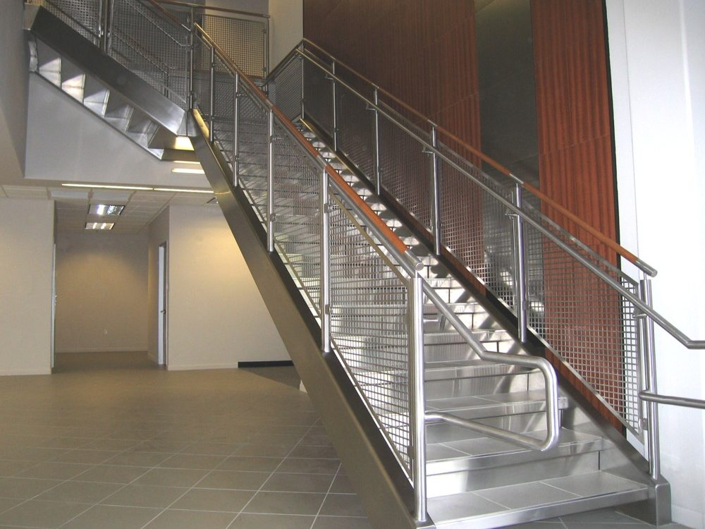 commercial building - stainless steel perf metal, railing, and stringer cladding. Stainless steel and wood cap rail.